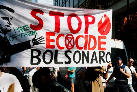 Climate activists hold a banner during a demonstration demanding protection for the Amazon rainforest outside the embassy of Brazil in Brussels